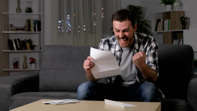 Excited man reading good news on letter Excited man reading good news on letter sitting on a couch in the living room at home in the night educational exam stock videos & royalty-free footage