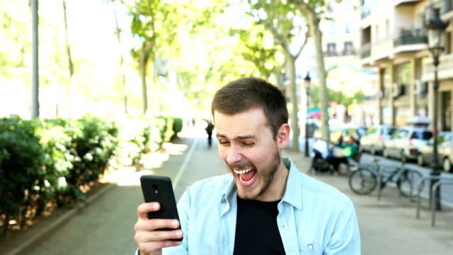 Excited man using phone and looks at camera Excited man using smart phone and after some time looks at camera celebrating good news incentive stock videos & royalty-free footage