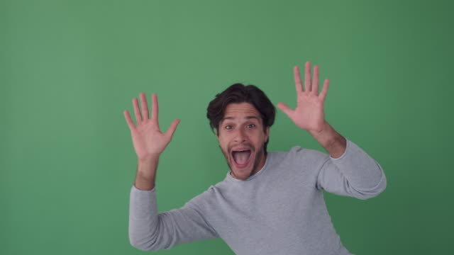 Excited man waving both hands on green background