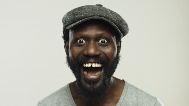 Excited mature man shouting against gray background Video of excited mature african man laughing against gray background. Close up footage of real black enjoying the moment. Studio 4K RAW video with sharp focus on eyes. excitement stock videos & royalty-free footage