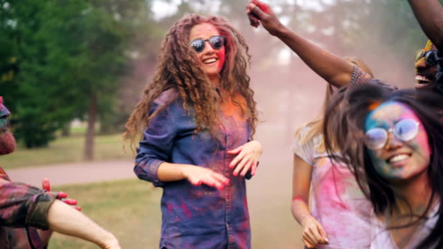 vídeos de stock e filmes b-roll de excited men and women are dancing at party covered with bright paint enjoying traditional indian holiday holi having fun and laughing. nature and culture concept. - holi