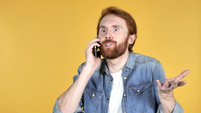 Excited Redhead Man Talking on Phone Isolated on Yellow Background