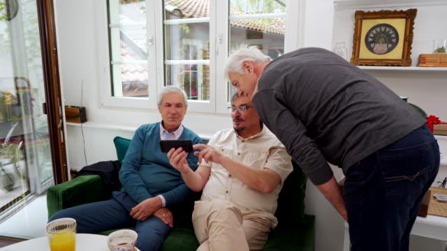 興奮した引退した高齢者は、携帯電話でゲームを見ながら、彼らのスポーツチームを応援 ビデオ