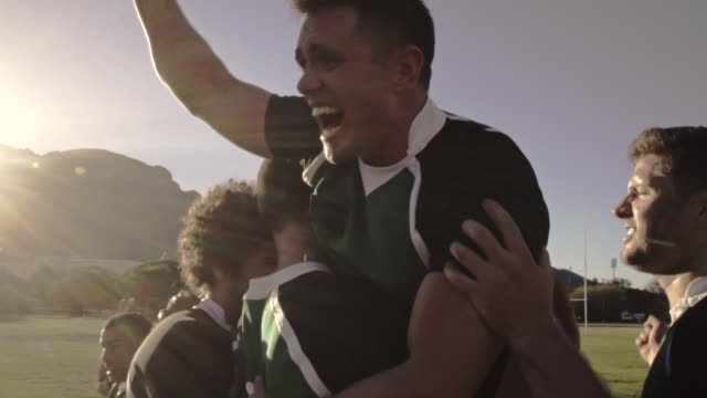 Excited rugby players celebrating the win Excited rugby players celebrating win at the field. Rugby team enjoying after the victory. rugby stock videos & royalty-free footage