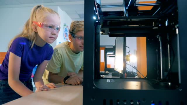 Excited school kids using three dimensional printer for creating 3D printed robot.