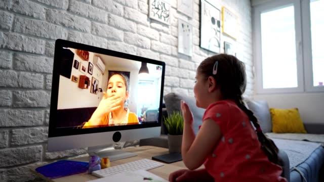 stockvideo's en b-roll-footage met opgewonden zusters zwaaien en blazen kussen tijdens videogesprek nadat ze geen tijd samen kunnen doorbrengen als gevolg van corona virus pandemie - corona scherm