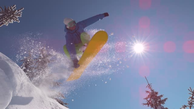 slow motion close up: excited snowboarder jumps over sun in mountain backcountry - snowboarding video stock e b–roll