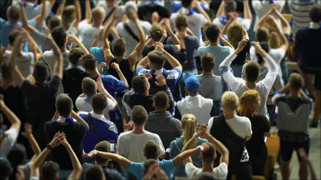 興奮したサッカーファンは、彼らのチーム、スポーツをサポートし、手を拍手 - 観客点の映像素材/bロール