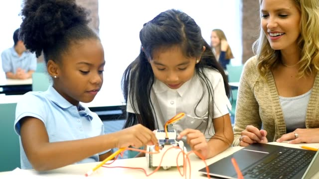 Excited STEM school girls build robot in technology class video
