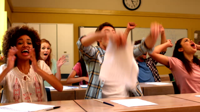 Excited students cheering in classroom Excited students cheering in classroom in slow motion educational exam stock videos & royalty-free footage