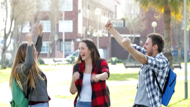 stockvideo's en b-roll-footage met opgewonden studenten springen vieren goed nieuws - student