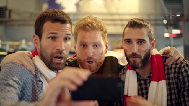 電話でサッカーの試合を見て興奮したサポーター - 注視する点の映像素材/bロール