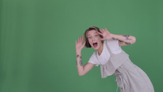 excited tattooed woman greeting hello with both hands over green screen - comparsa video stock e b–roll