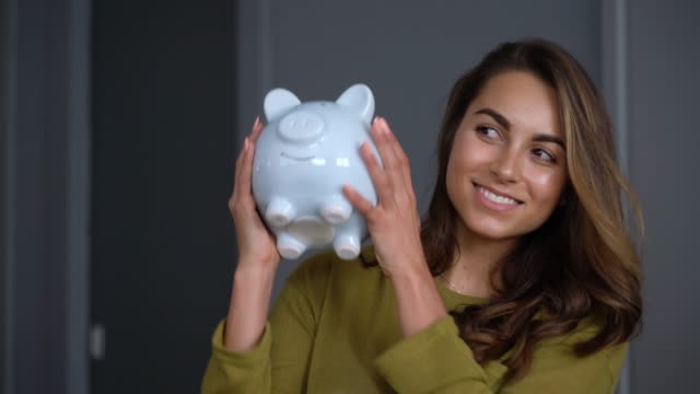 Excited woman at home shaking her piggy bank smiling Excited woman at home shaking her piggy bank smiling very happy piggy bank stock videos & royalty-free footage