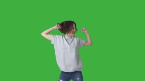 aufgeregte frau feiert erfolg über grünen hintergrund - feiern stock-videos und b-roll-filmmaterial