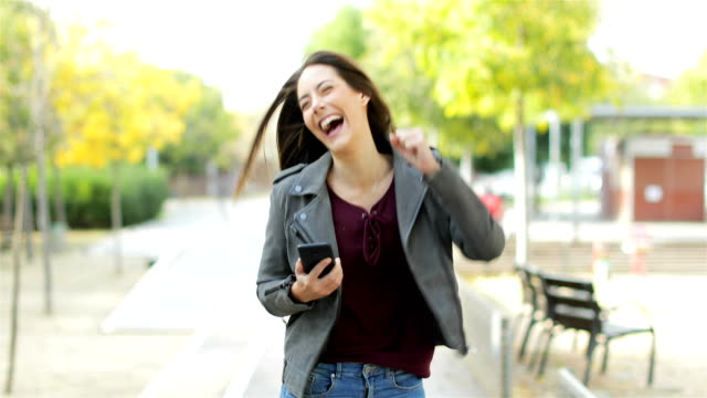 Excited woman checking phone celebrating good news Front view of an excited woman walking towards camera, checking phone and celebrating good news in a park good news stock videos & royalty-free footage