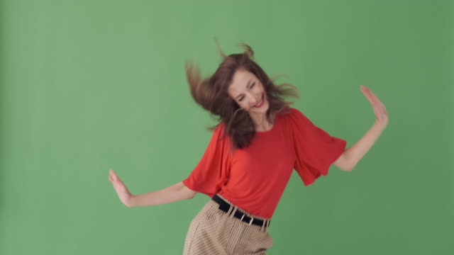 excited woman dancing over green background - comparsa video stock e b–roll