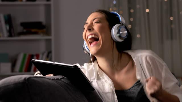 vídeos y material grabado en eventos de stock de mujer muy contenta de encontrar contenidos online en tablet - descargar internet