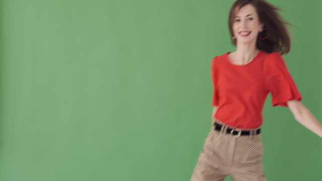 excited woman greeting hello over green background - comparsa video stock e b–roll