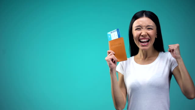 Excited woman holding passport with tickets in hand, winning vacation tour Excited woman holding passport with tickets in hand, winning vacation tour passport stock videos & royalty-free footage