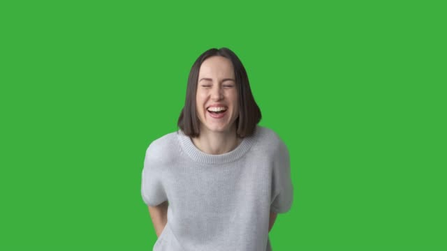 Excited woman laughing out loud Excited young woman laughing out loud over green chroma key background physical position stock videos & royalty-free footage
