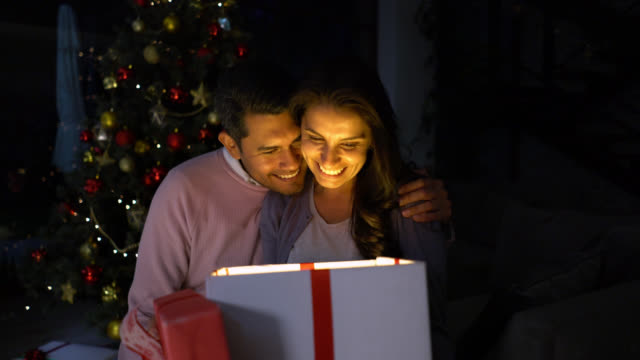 Excited woman opening her christmas present from partner while he kisses her on the cheek