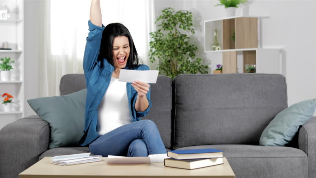 excited woman reading a voucher at home - bills and taxes stock videos & royalty-free footage