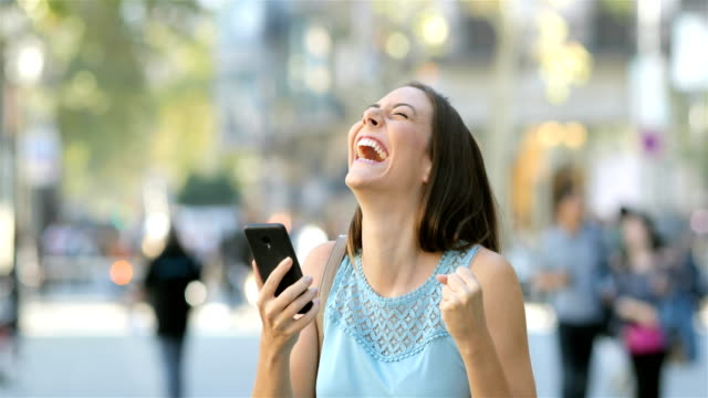 excited woman reading news in a phone in the street - euforia video stock e b–roll