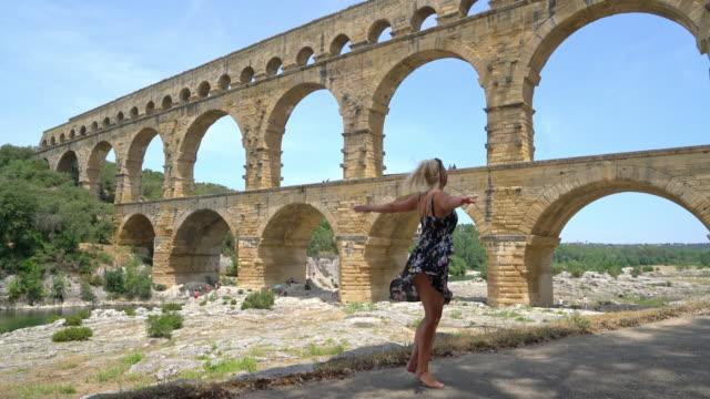 stockvideo's en b-roll-footage met ws opgewonden vrouw twirling door de pont du gard - pont du gard