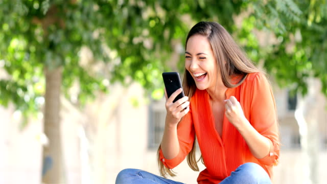 excited woman using a phone in a park - vincere video stock e b–roll