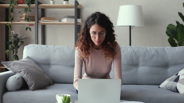 Excited woman winner looking at laptop celebrating success at home Excited young woman winner looks at laptop celebrates online success sits on sofa at home. Euphoric lady gets new distance job opportunity, reads good news in email, rejoices victory, feels motivated. ecstatic stock videos & royalty-free footage