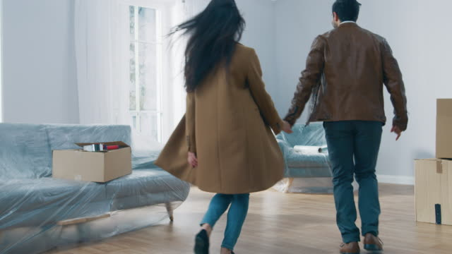 vídeos de stock e filmes b-roll de excited young couple holding hands enters newly purchased / rented apartment, they start happily embracing and dancing. bright modern home for happy young people. - future hug
