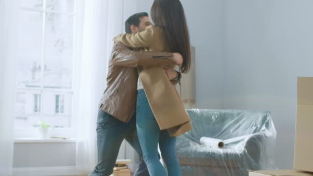 excited young couple look around in wonder at their newly purchased / rented apartment. beautiful people happily embracing. bright modern home for happy young people. - proprietario d'immobili video stock e b–roll