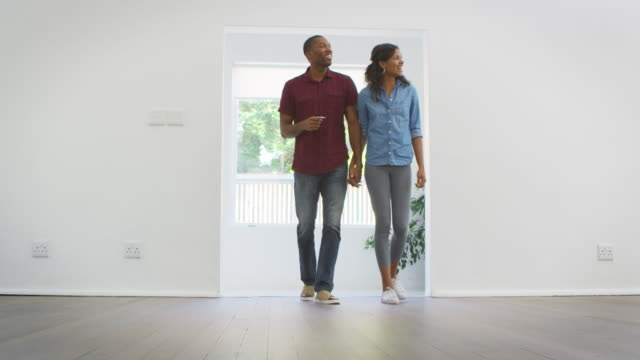 excited young couple moving into new home together - esploratore video stock e b–roll