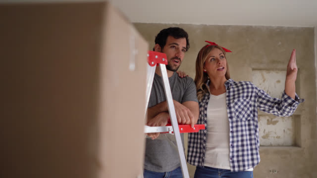 Excited young couple planning their home renovation talking and pointing away very happy Excited young couple planning their home renovation talking and pointing away very happy and smiling renovation stock videos & royalty-free footage