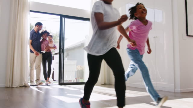 Excited young family exploring new home on moving in day - shot in slow motion