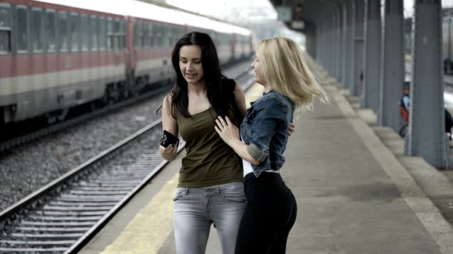 Excited young girls arriving and meeting in train station and taking a selfie pictures with smartphone