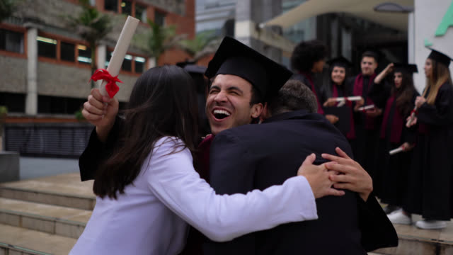 Excited young man running towards parents hugging them after receiving his college diploma all smiling
