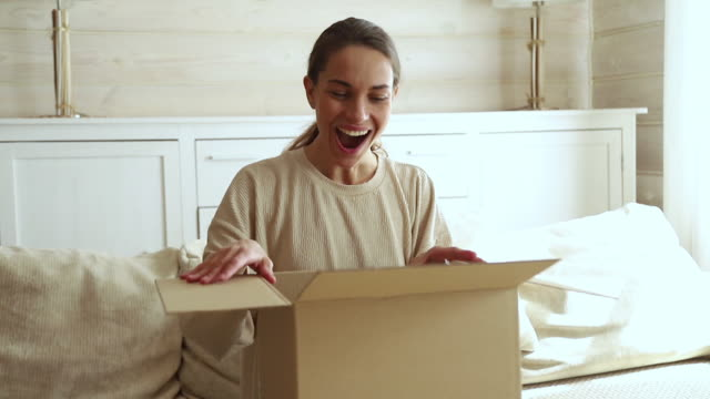 Excited young woman consumer open cardboard box get postal parcel