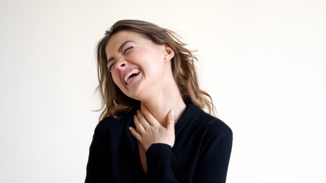 Excited young woman laughing at studio Close-up of excited young woman laughing against white background in studio laughing stock videos & royalty-free footage