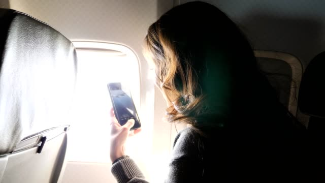 Excited young woman snaps photos while on airplane Excited young adult female tourist uses smartphone to take photos during landing on airplane. landing touching down stock videos & royalty-free footage