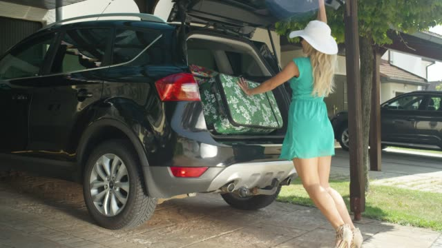 SLOW MOTION: Excited young woman struggles to close the trunk of her black SUV. SLOW MOTION, LENS FLARE: Excited young woman struggles to close the trunk of her black SUV after packing too much luggage for her trip. Funny shot of girl trying to close the back of her big car. stuffed stock videos & royalty-free footage