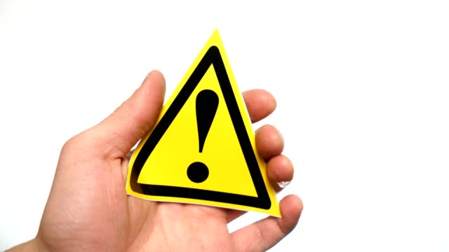 Exclamation mark sign isolated. Male hand showing warning yellow sign