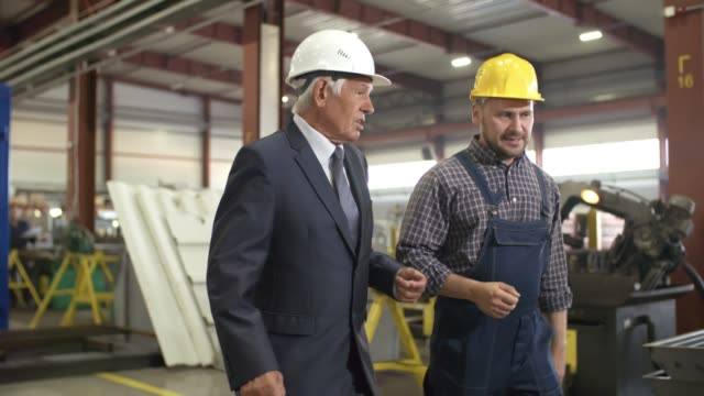 Direction et ingénieur inspectant les locaux de l'usine - Vidéo
