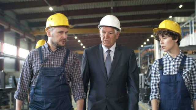 fabrika boyunca yürüyen yönetici ve mühendisler - ziyaret stok videoları ve detay görüntü çekimi
