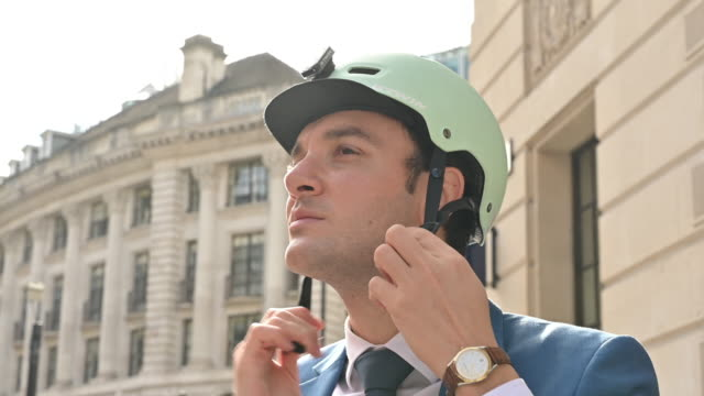 Executive checking smart phone and putting on bicycle helmet