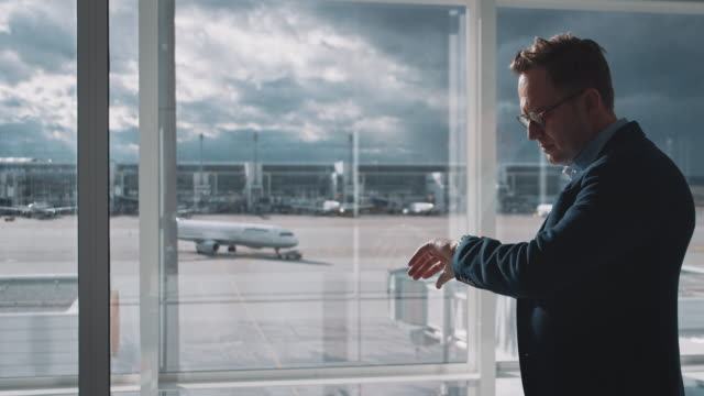 Executive checking time while waiting at airport Businessman looking at airplane through window. Male professional is checking time on wristwatch. He is waiting at airport. instrument of time stock videos & royalty-free footage