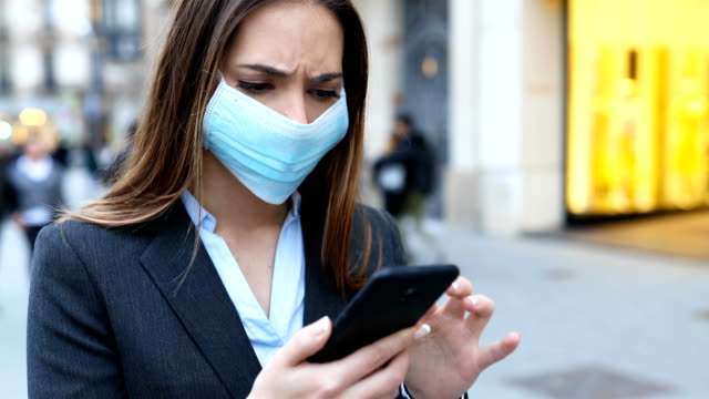 Executive wearing mask checking news on phone