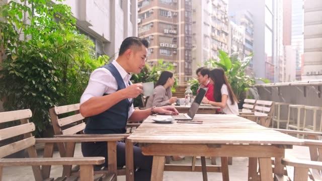 vidéos et rushes de executive avec la tasse de café et les technologies au café - man drinking terrace