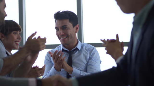executives applauding in a business meeting ,Cheerful business group applaud speaker in seminar